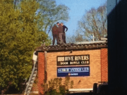 Image shows workers on a roof with no edge protection HSE