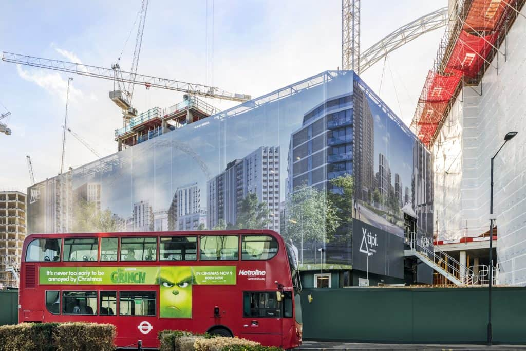Image showing a printed building wrap hiding scaffolding with a red bus